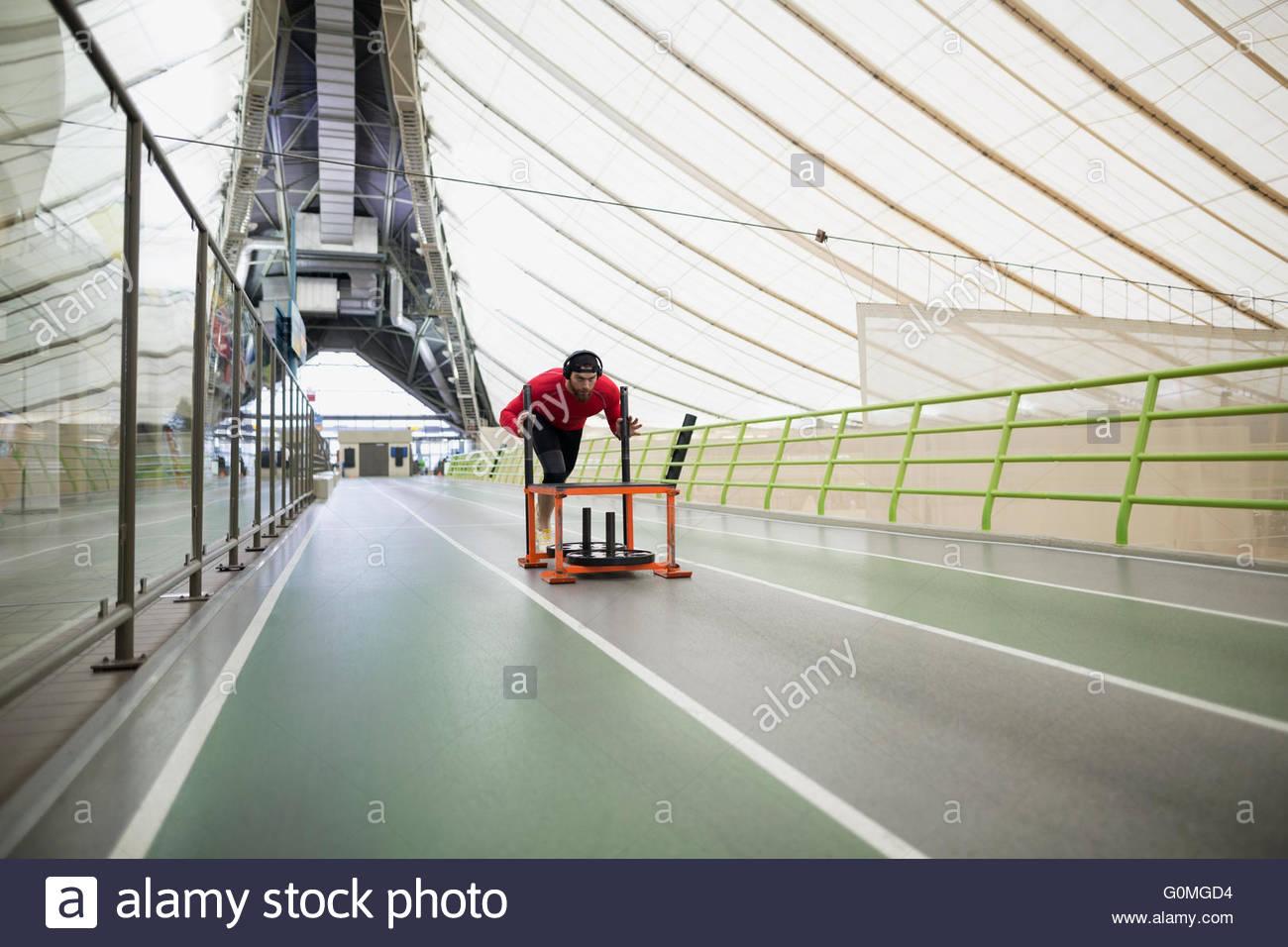 Läufer sprinten Schlitten auf indoor-Bahn schieben Stockbild