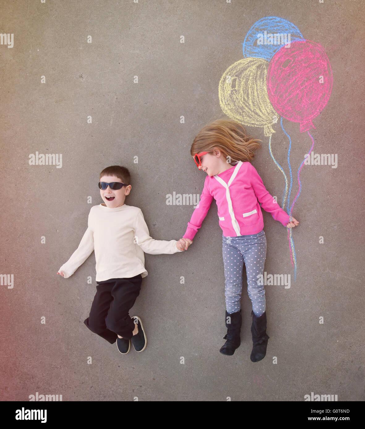 Kinder halten Händchen im Außenbereich mit bunter Kreide Luftballons skizziert auf Zement für eine Stockbild