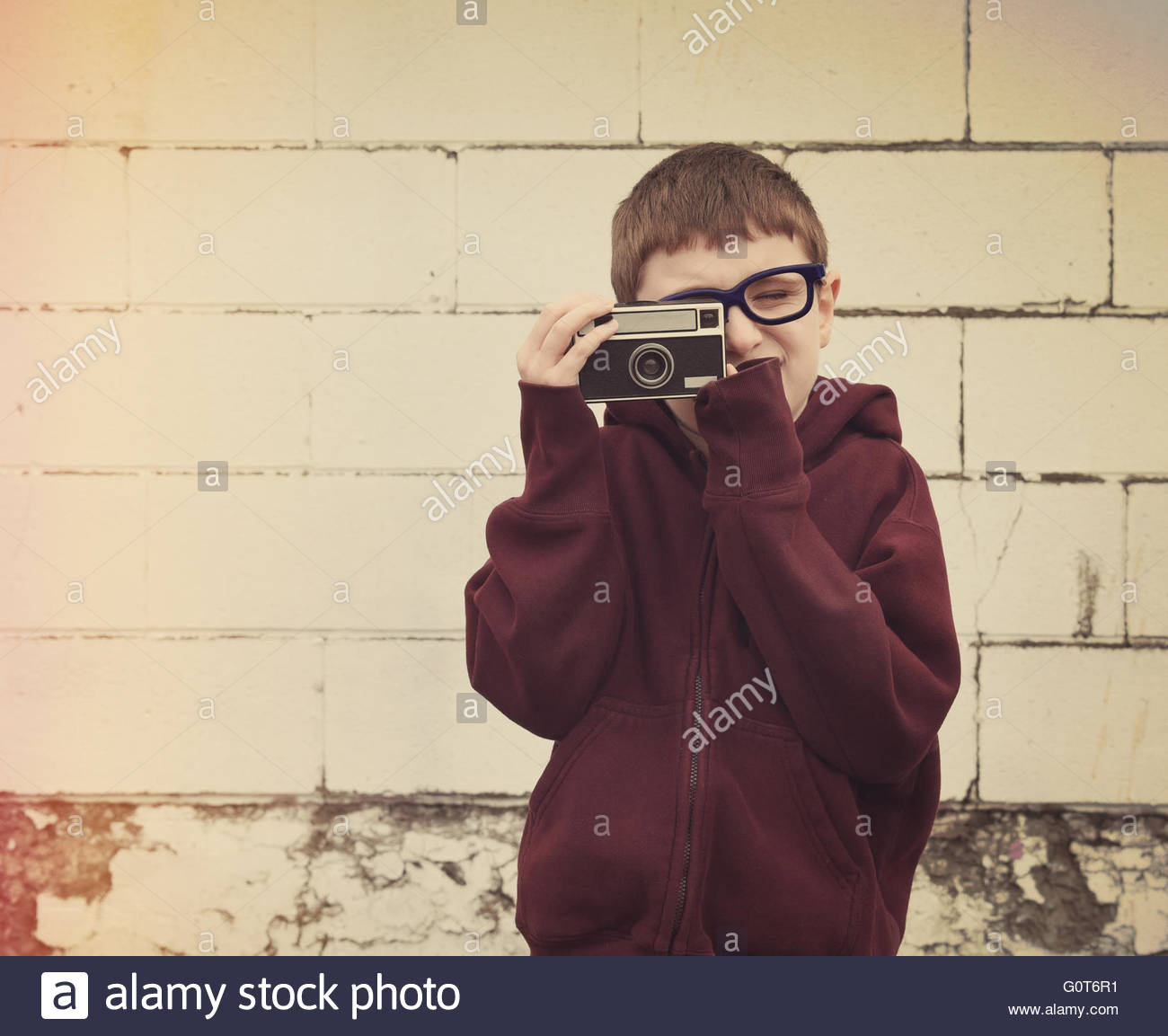 Ein junges Kind nimmt ein Foto mit einer alten Vintage-Kamera gegen eine Mauer für ein Retro-Technologie oder Stockbild