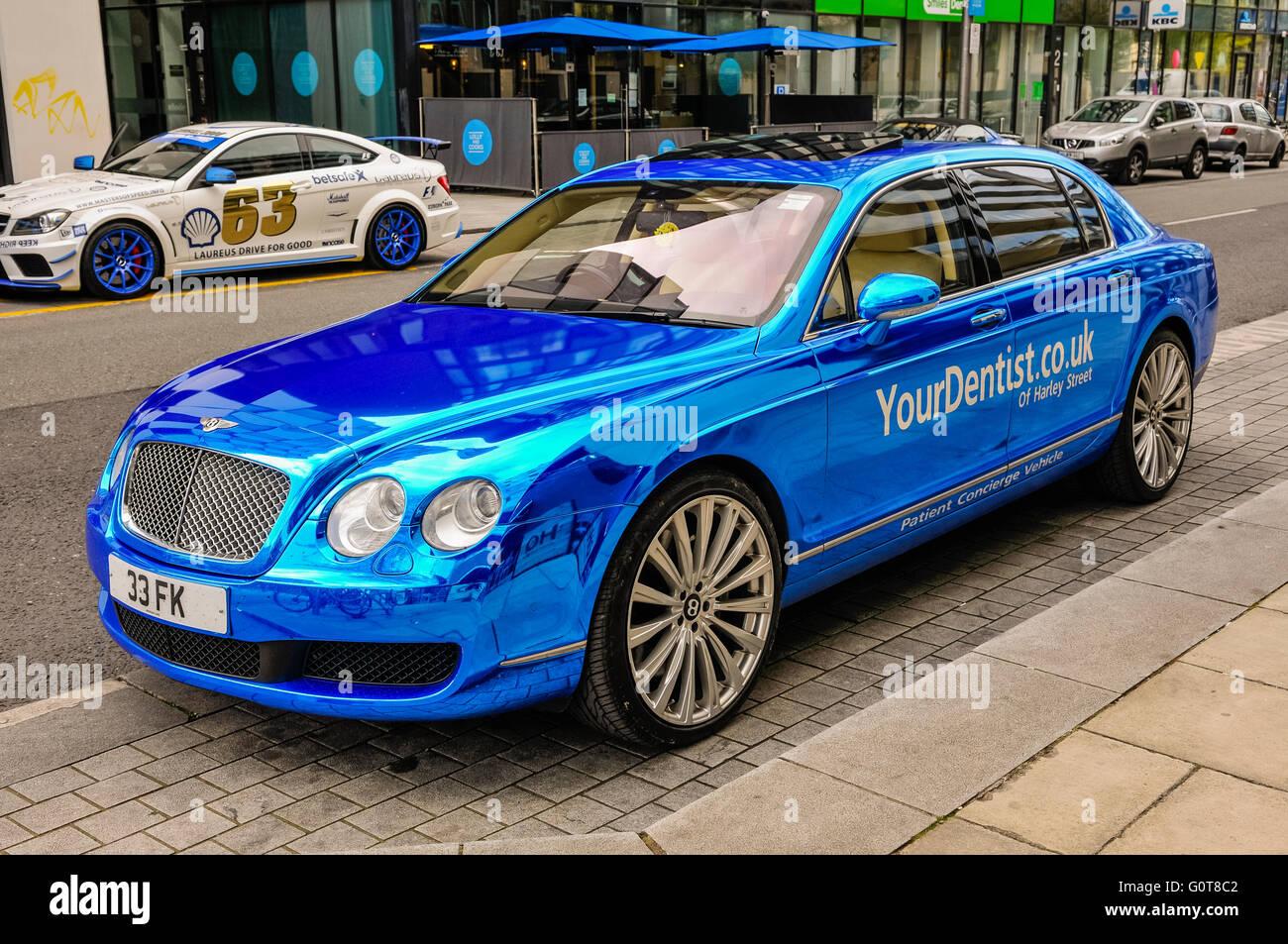 Ein Bentley Flying Spur mit blauer gespiegelten Farbe, Concierge Fahrzeug für YourDentist.co.uk der Harley Stockbild