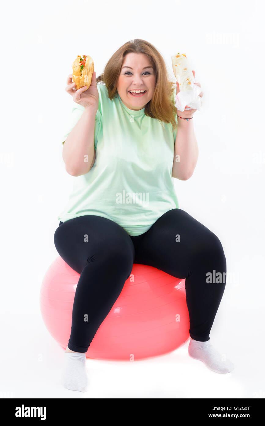 Korpulente Frau, die sucht nach ungesunden Essen sitzen auf Fitness-ball Stockbild