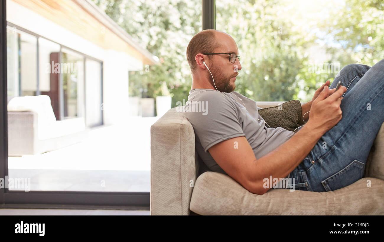 Side-View-Bild eines Mannes mit seinem Tablet beim Sitzen auf dem Sofa zu Hause. Entspannen Sie sich auf die Couch Stockbild