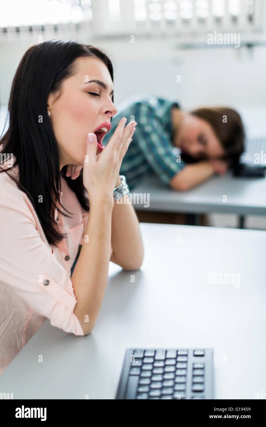 Junge schöne Mädchen während des Unterrichts von Langeweile und Müdigkeit Gähnen Stockbild