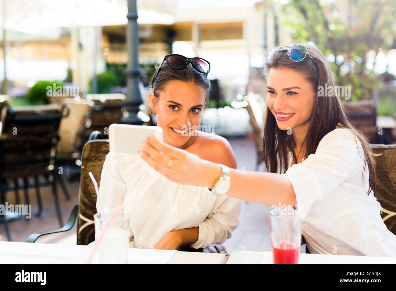 Zwei junge schöne Frauen, die eine Selfie von sich selbst in der Mittagspause Stockbild