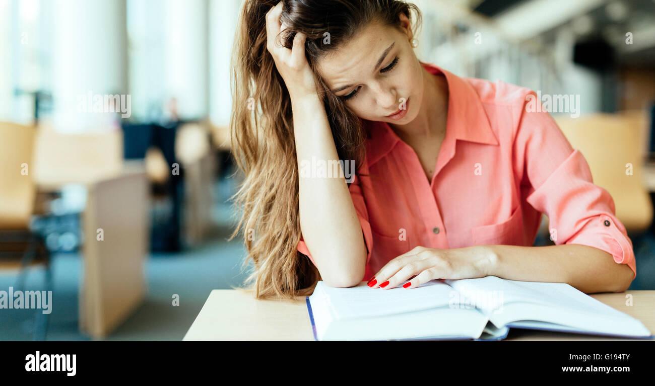 Weibliche Studenten studieren und lesen in einer Bibliothek aber ist eine harte Zeit Verständnis des Materials Stockbild