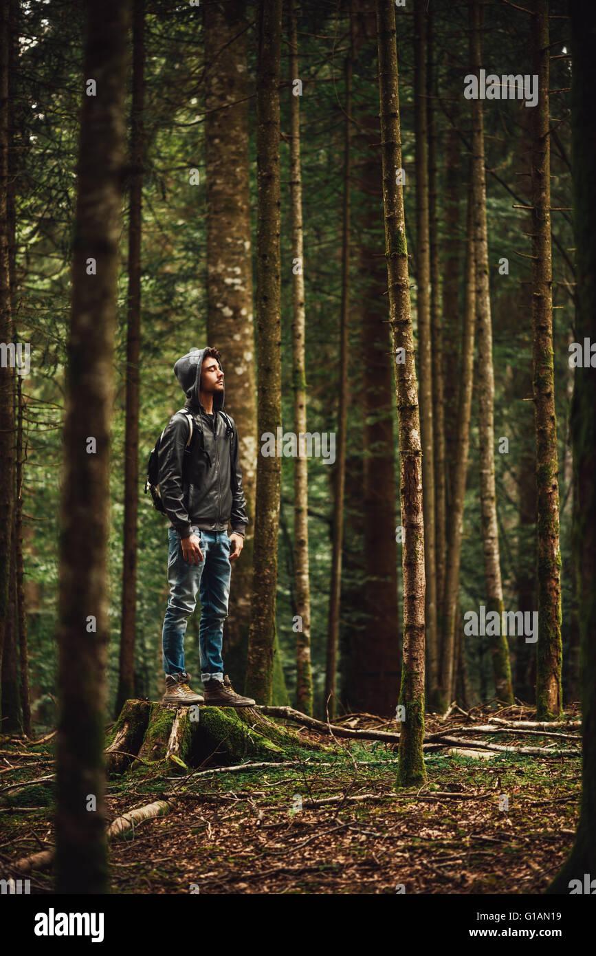 Vermummte jungen Mann im Wald stehen und erkunden, Freiheit und Natur-Konzept Stockbild