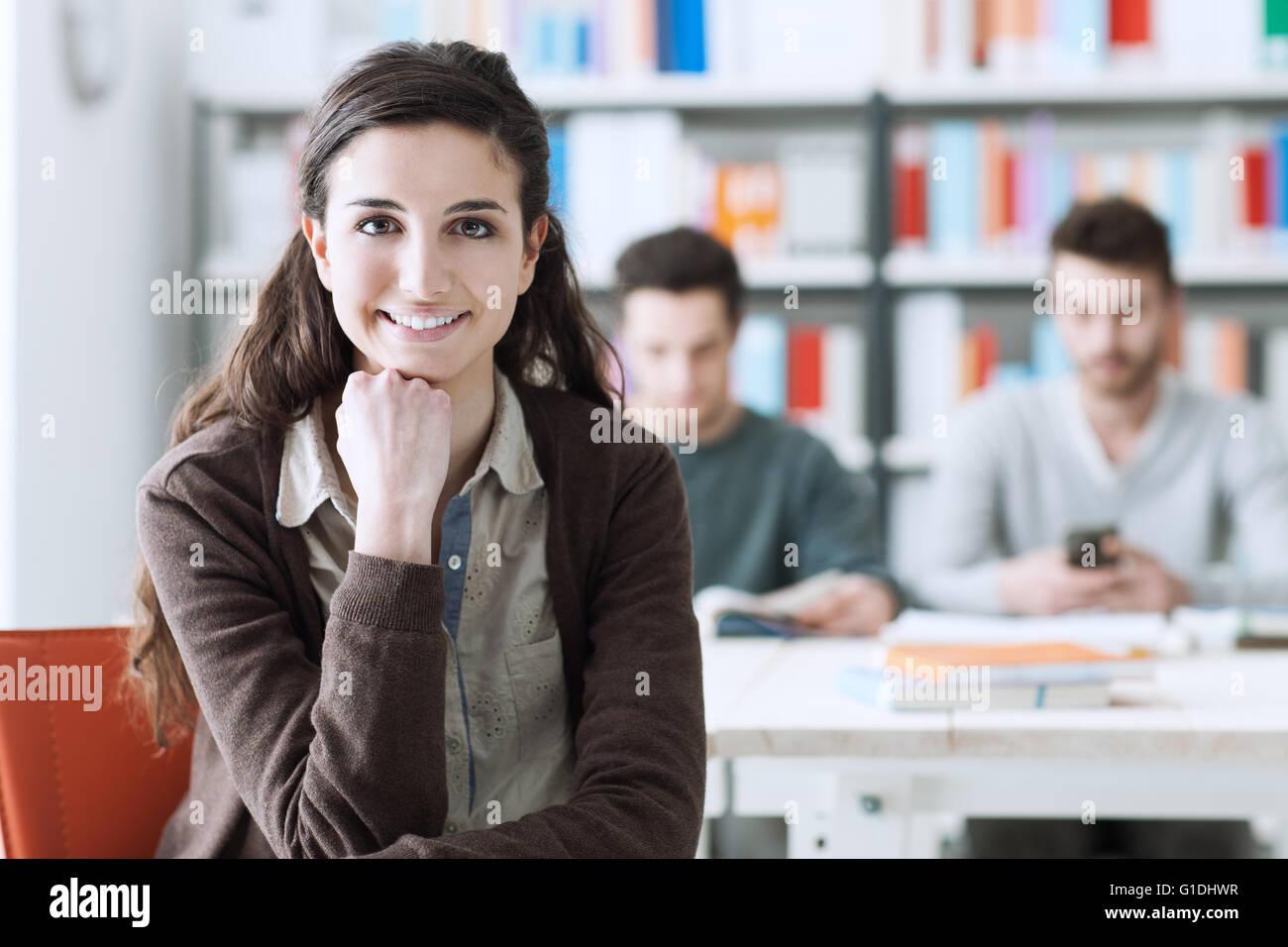 Jungen Student an der Bibliothek, Blick in die Kamera Lächeln, sitzen ihre Mitschüler am Schreibtisch Stockbild