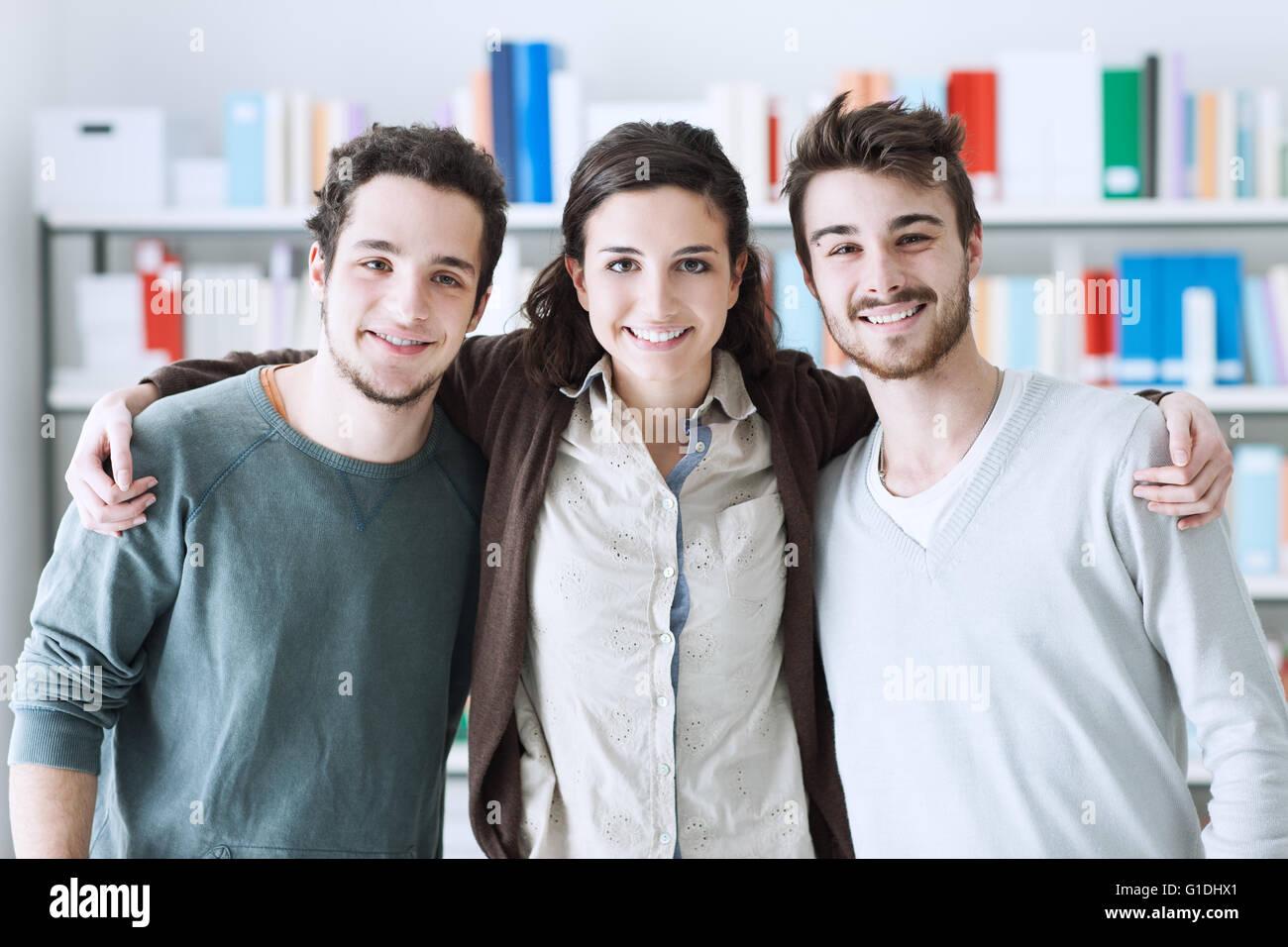 Teenager-Freunde in der Bibliothek zusammen posieren und umarmt, Jugend- und Freundschaft Konzept Stockbild