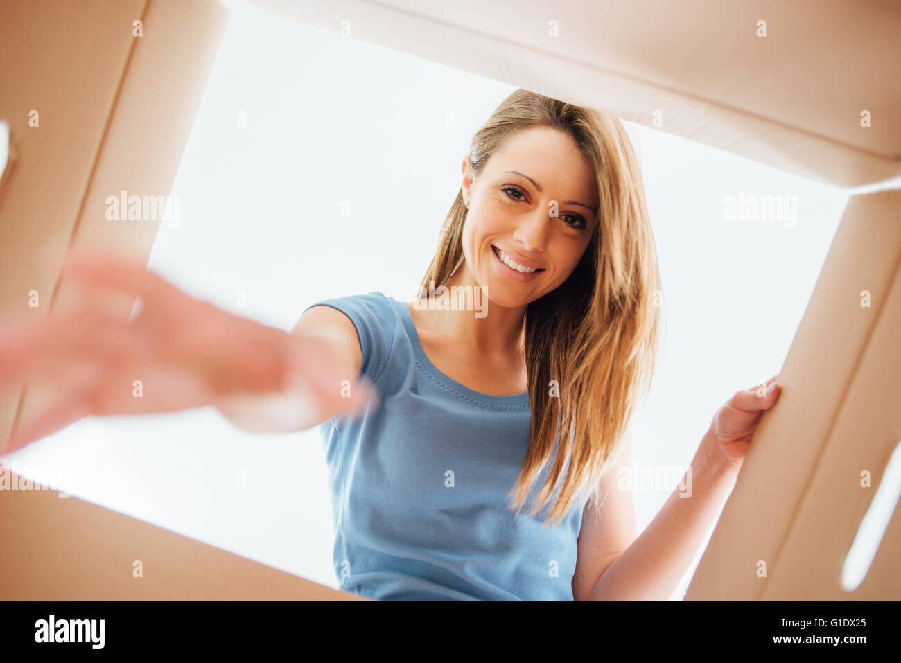 Lächelnde junge Frau einen Karton, Umzug öffnen und Auspacken Konzept Stockbild