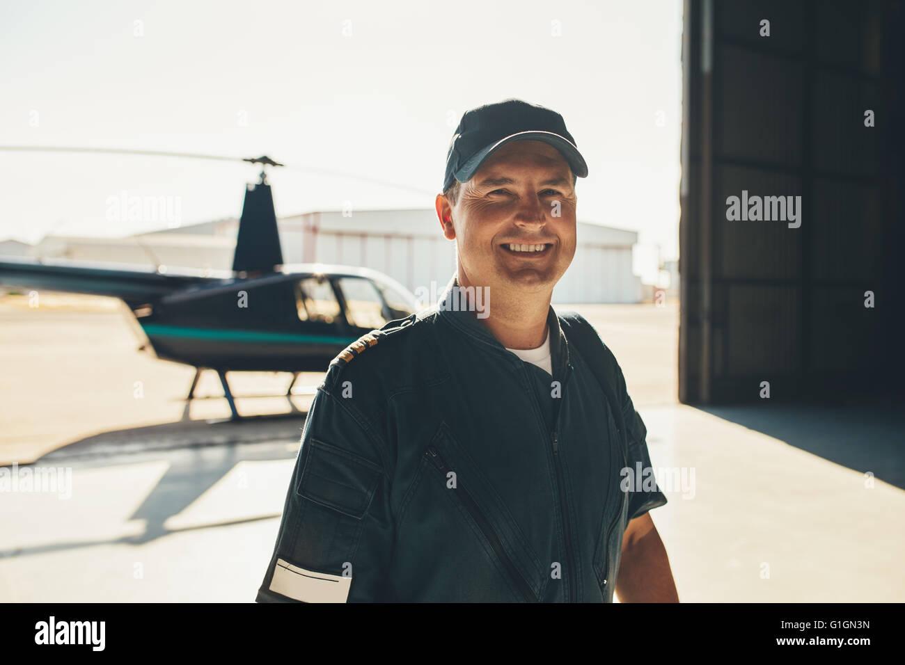Porträt von glücklich männliche Piloten stehen im Flugzeughangar mit einem Hubschrauber im Hintergrund Stockbild
