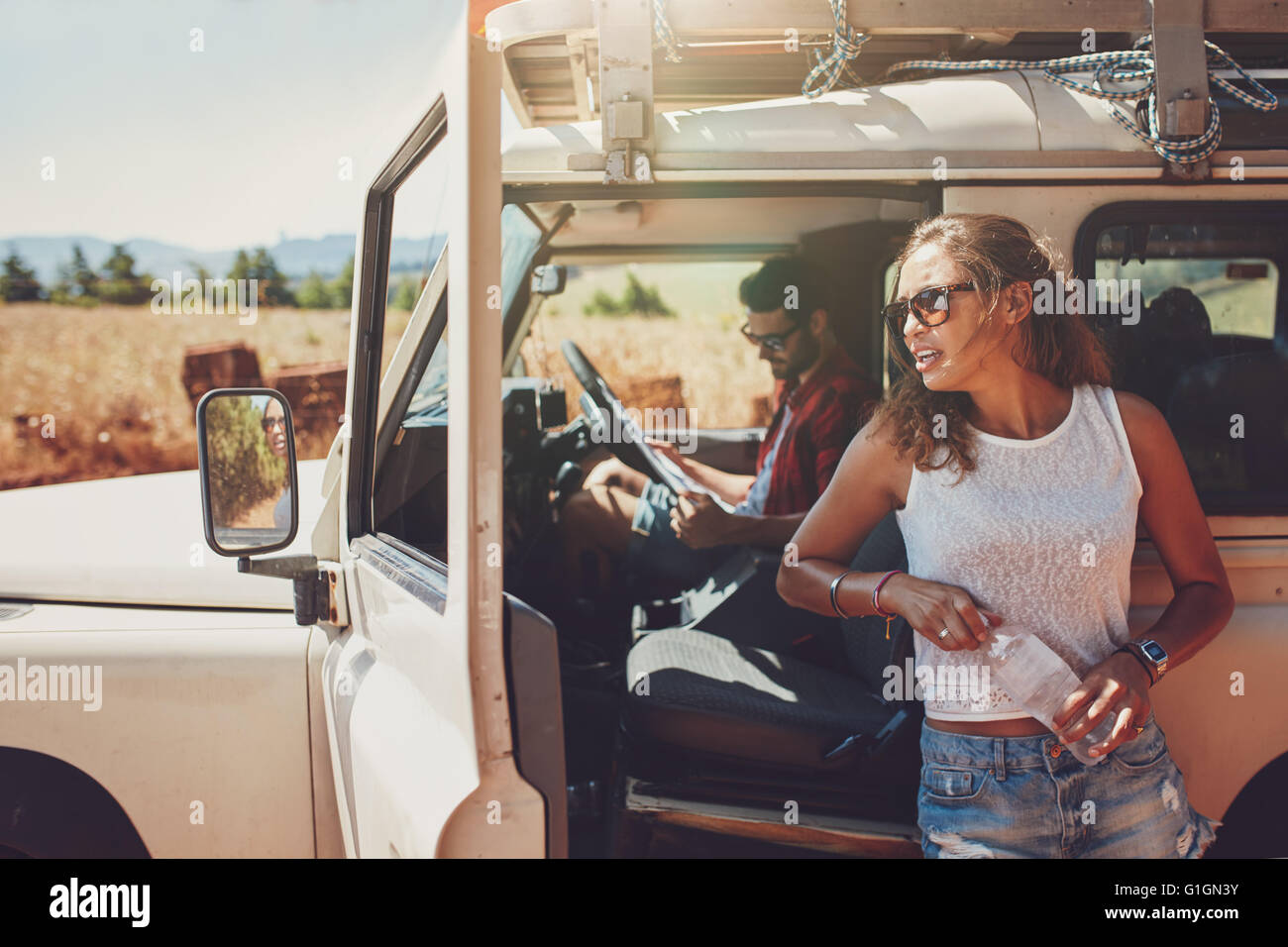 Junge Frau, die außerhalb des Autos hält eine Flasche Wasser mit Mann sitzt auf dem Fahrersitz Blick auf Stockbild