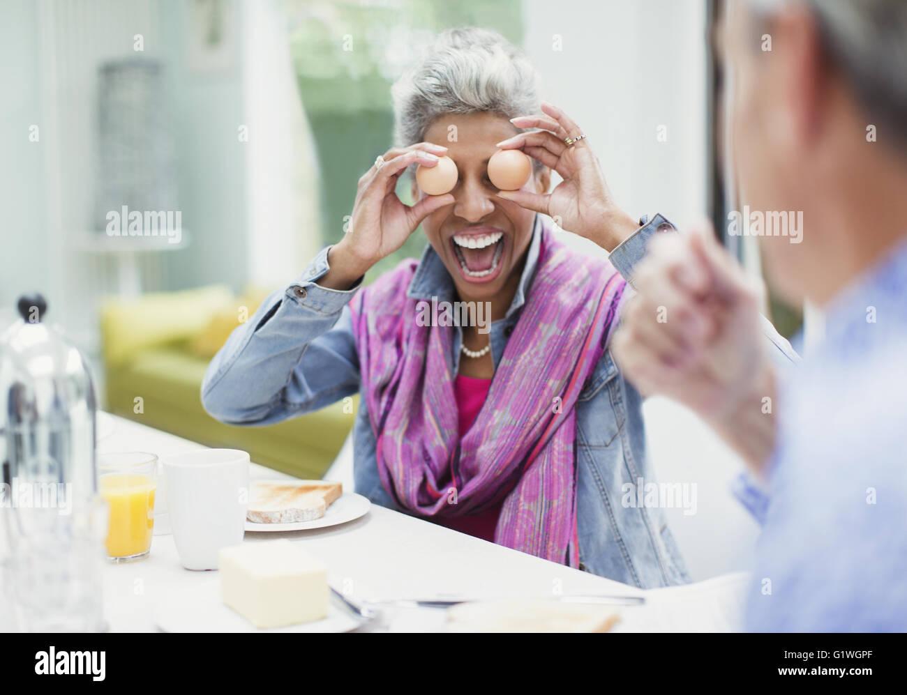 Spielerische Reife Frau für Augen mit Eiern am Frühstückstisch Stockbild