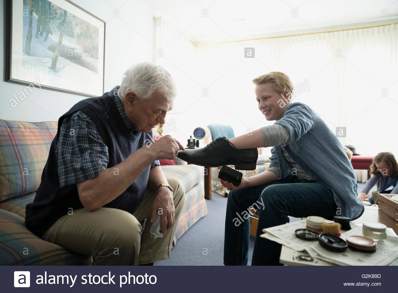 Großvater Inspektion Schuhe poliert von Enkel Stockbild