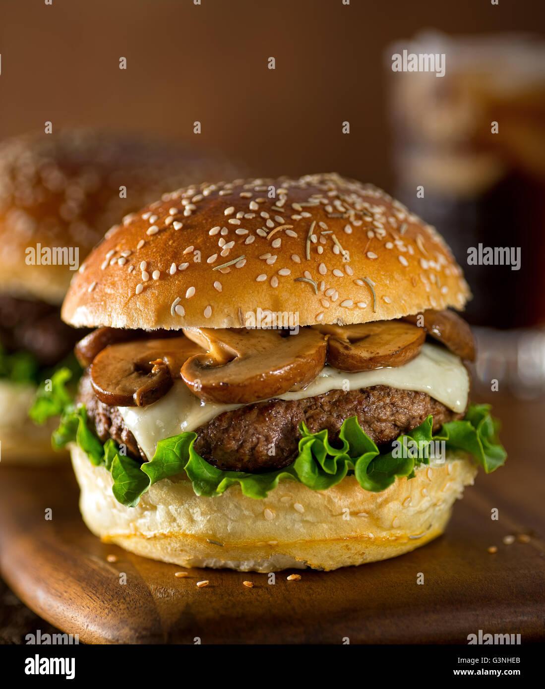 Ein köstliches Gourmet-Hamburger mit Schweizer Käse und gebratenen Champignons auf ein Rosmarin Sesam Stockbild