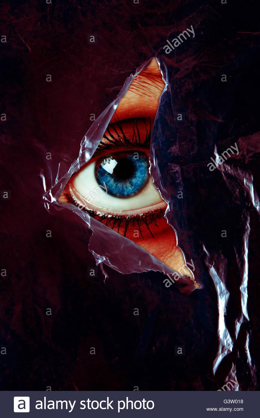 blaues Auge einer Frau hinter einer zerrissenen Plastikfolie Stockfoto
