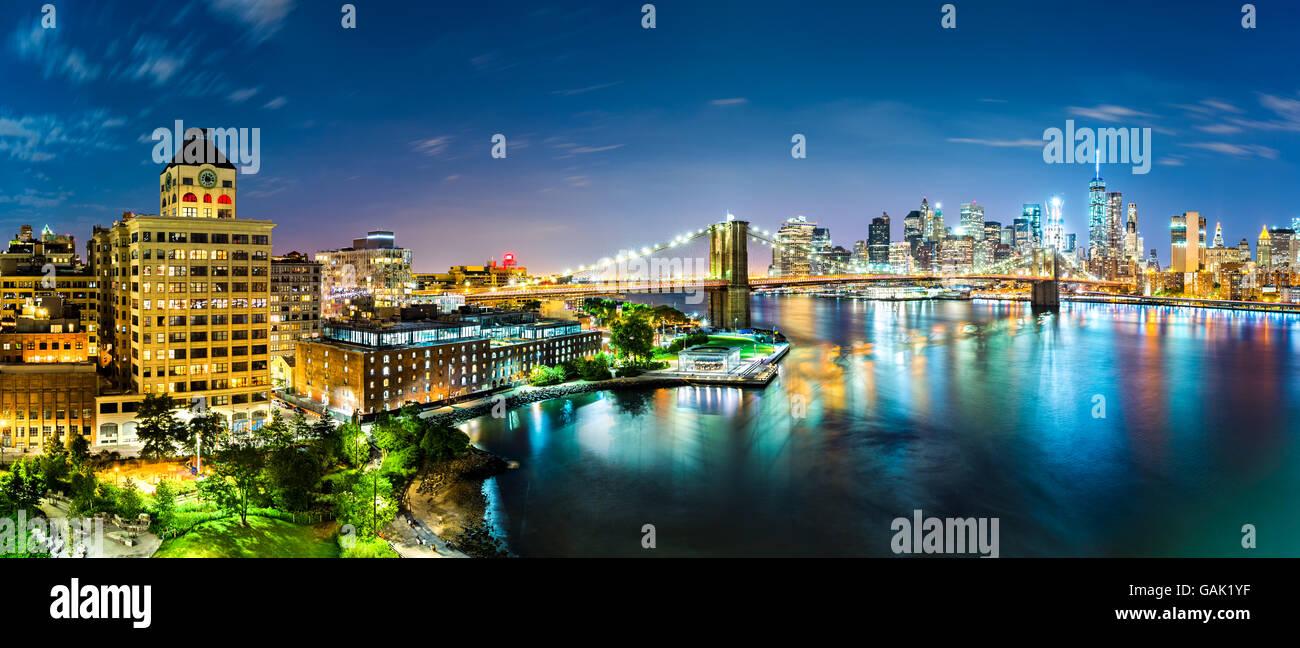 New York City Panorama bei Nacht. Brooklyn Bridge überspannt East River zwischen Manhattan und Brooklyn Bezirke Stockbild