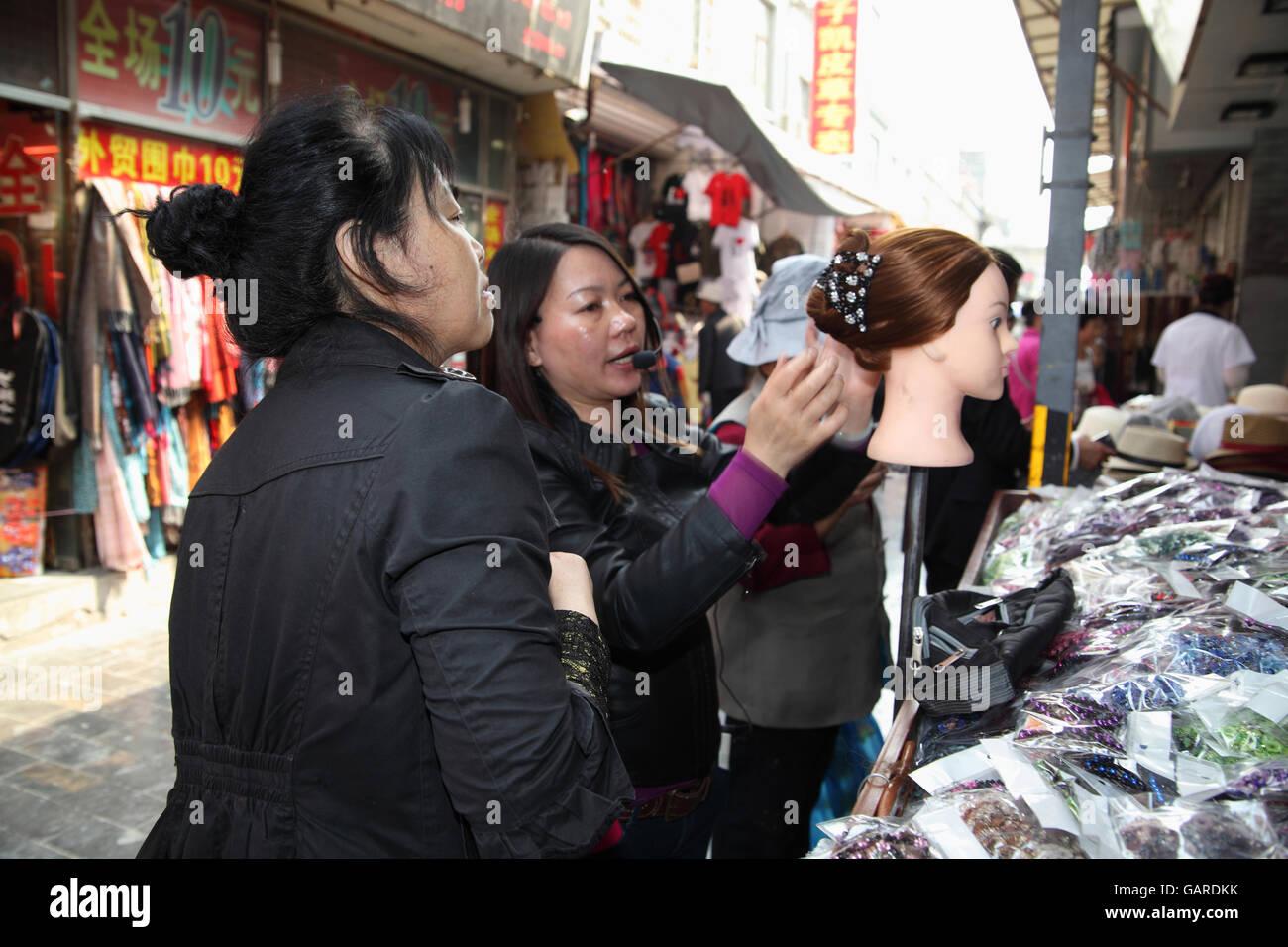 Eine Frau kämmt und eine Schaufensterpuppe in einer Galanterie zusammen eine Perücke aufsetzt, sie spricht Stockbild
