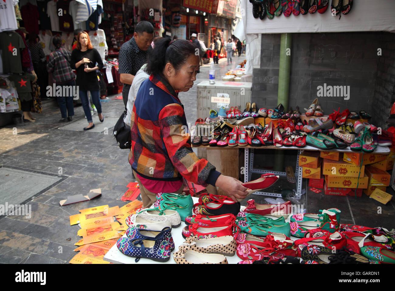 Eine Chinesin ist in einem offenen Markt betrachtet man billige Schuhe, die sie kaufen kann. Qibao Old Street. Peking, Stockbild