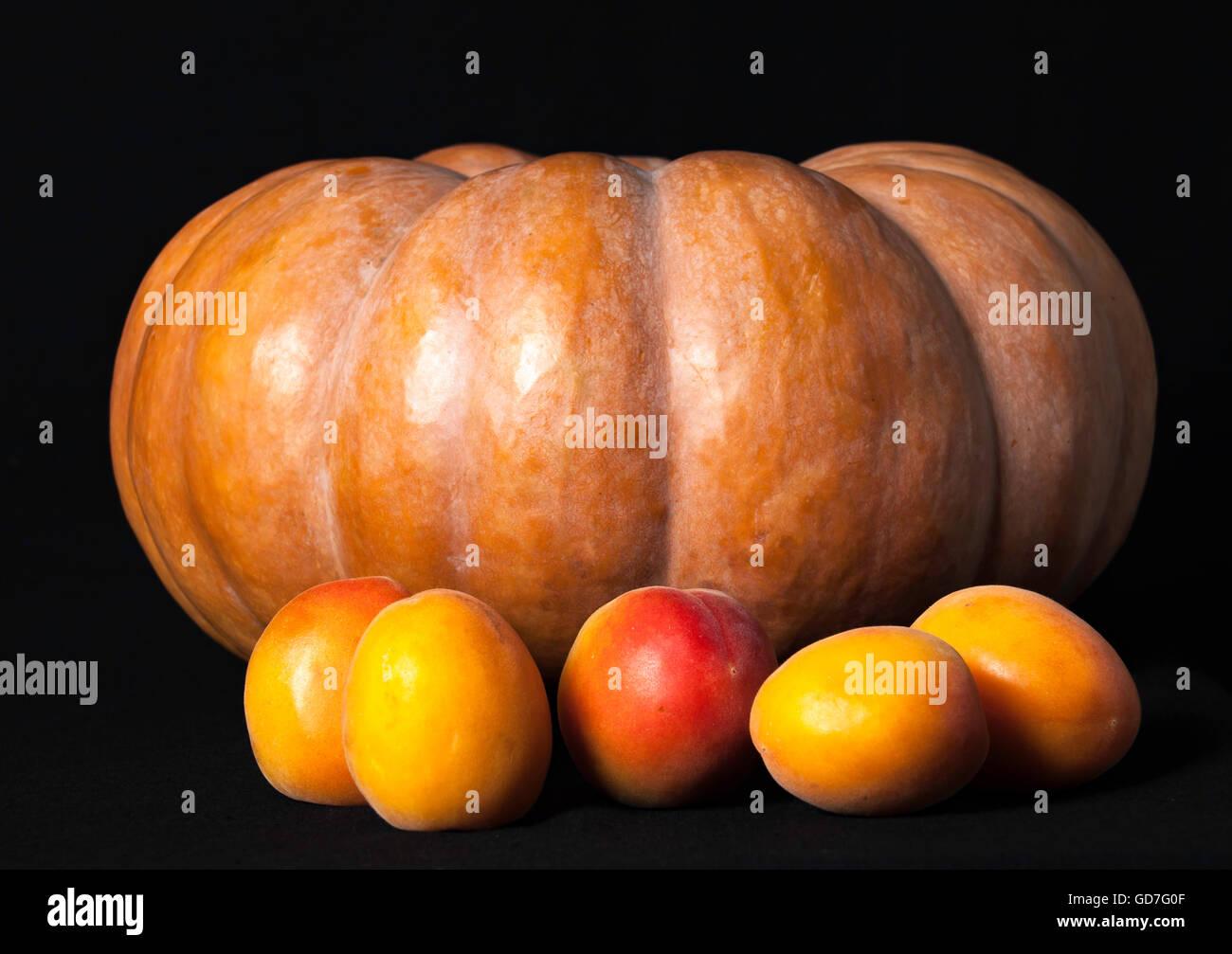 Kürbis und 5 Pfirsiche auf schwarzem Hintergrund im Studio fotografiert Stockbild