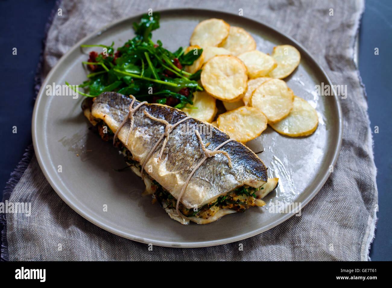 Gefüllter Seebarsch mit Salat und Kartoffeln Stockbild