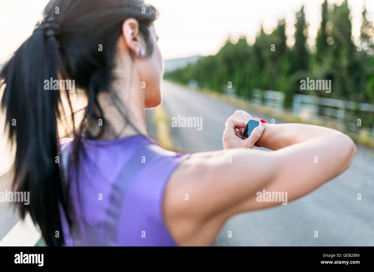 Frau Adjustung Einstellungen des smart-Uhr für outdoor-training Stockbild