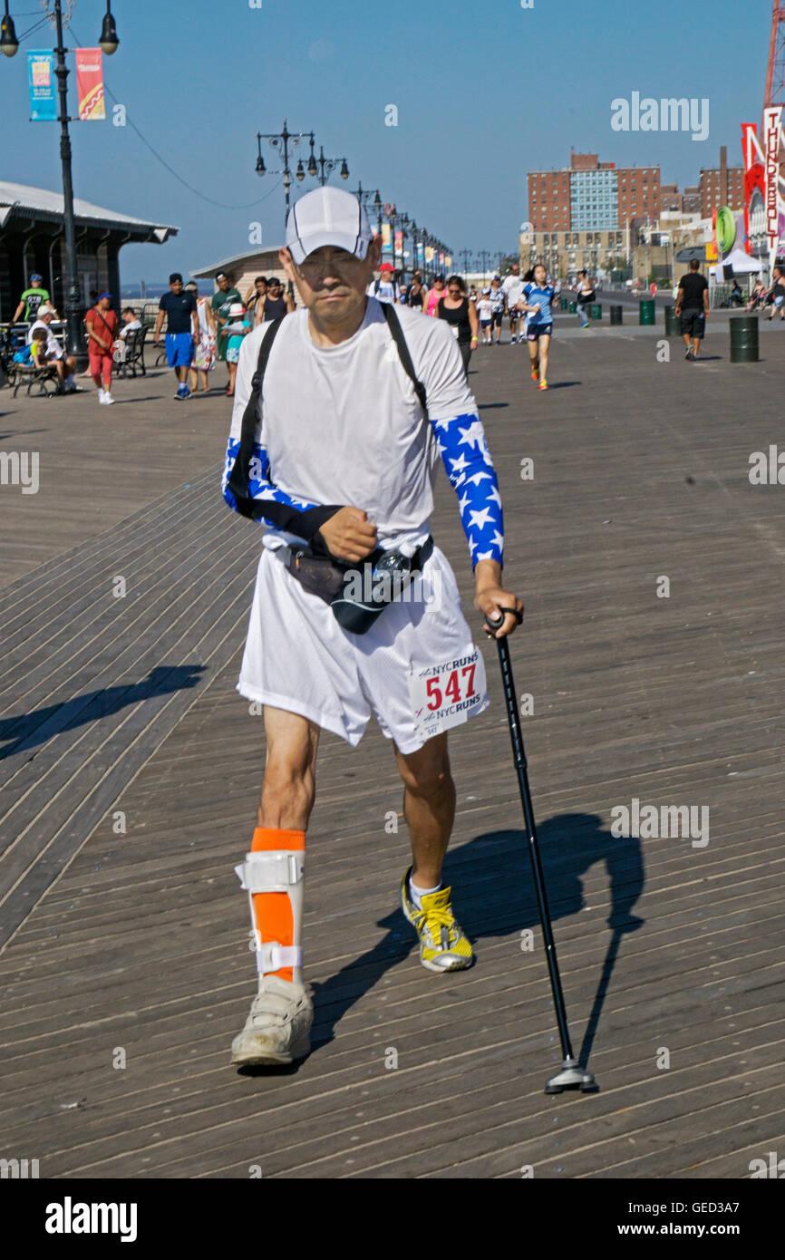 Ein verletzter Mann mit einem Rohrstock und Besetzung geht in der NYRRC 5K laufen auf der Reigelmann-Promenade in Stockbild