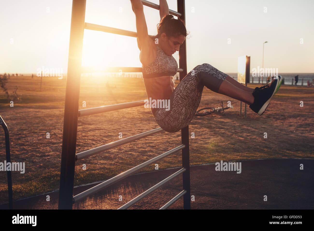 Offenen Schuß wirklich gesund und Fit Frau Durchführung hängende Bein hebt auf outdoor-Fitness-Station Stockbild