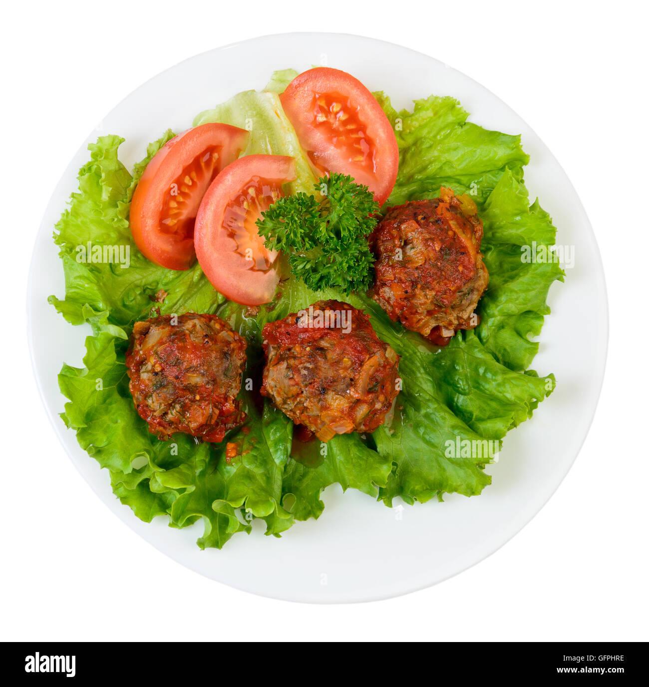 Gebratene Fleischbällchen mit Gemüse und Kräutern auf Platte isoliert auf weiss Stockbild
