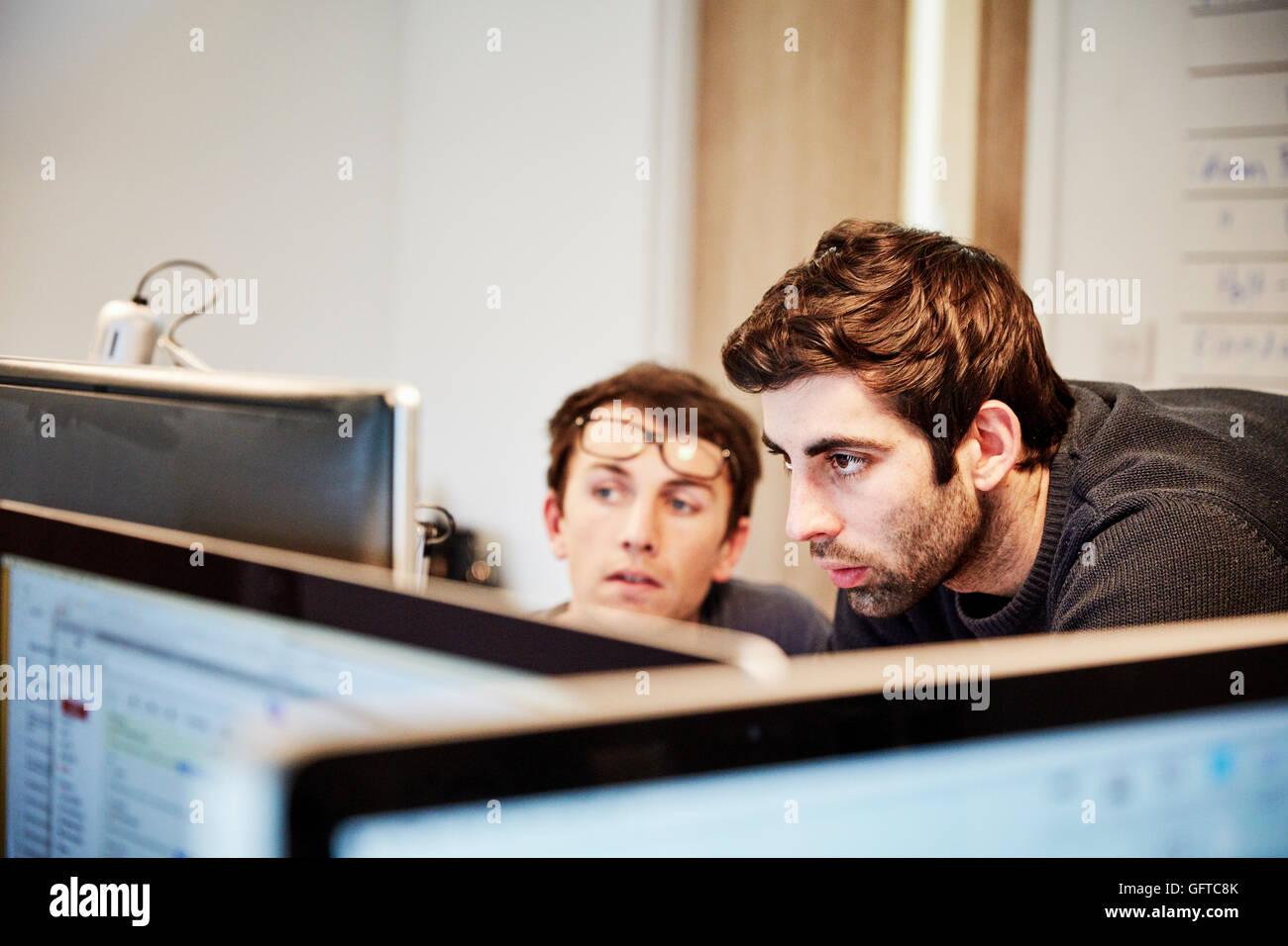 Möbelwerkstatt, zwei Personen, eine Design unter Bezugnahme auf Zeichnungen und Laptop-Computern zu diskutieren Stockbild