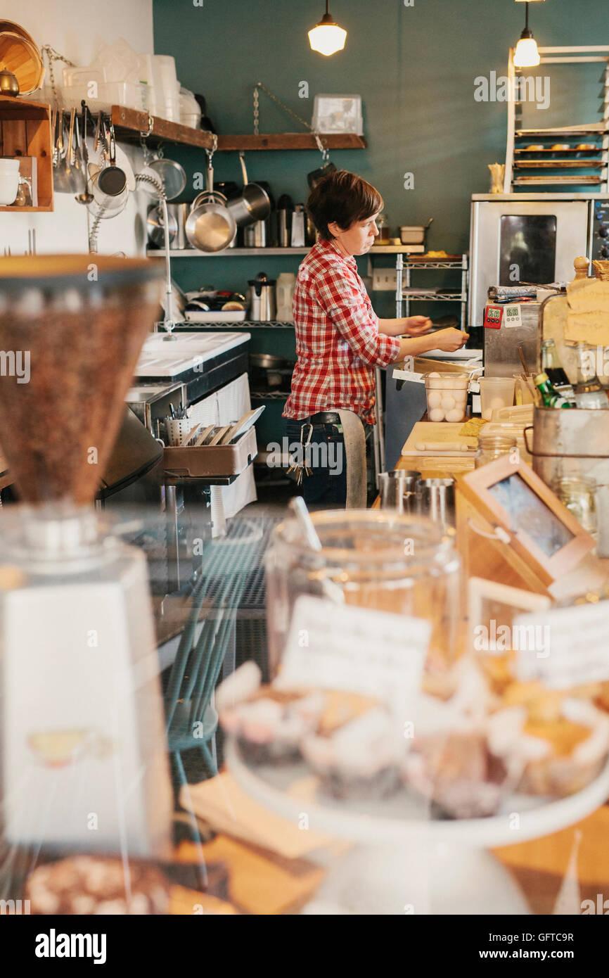 Eine Frau in einem karierten Hemd hinter dem Tresen in einem Café arbeiten Stockbild