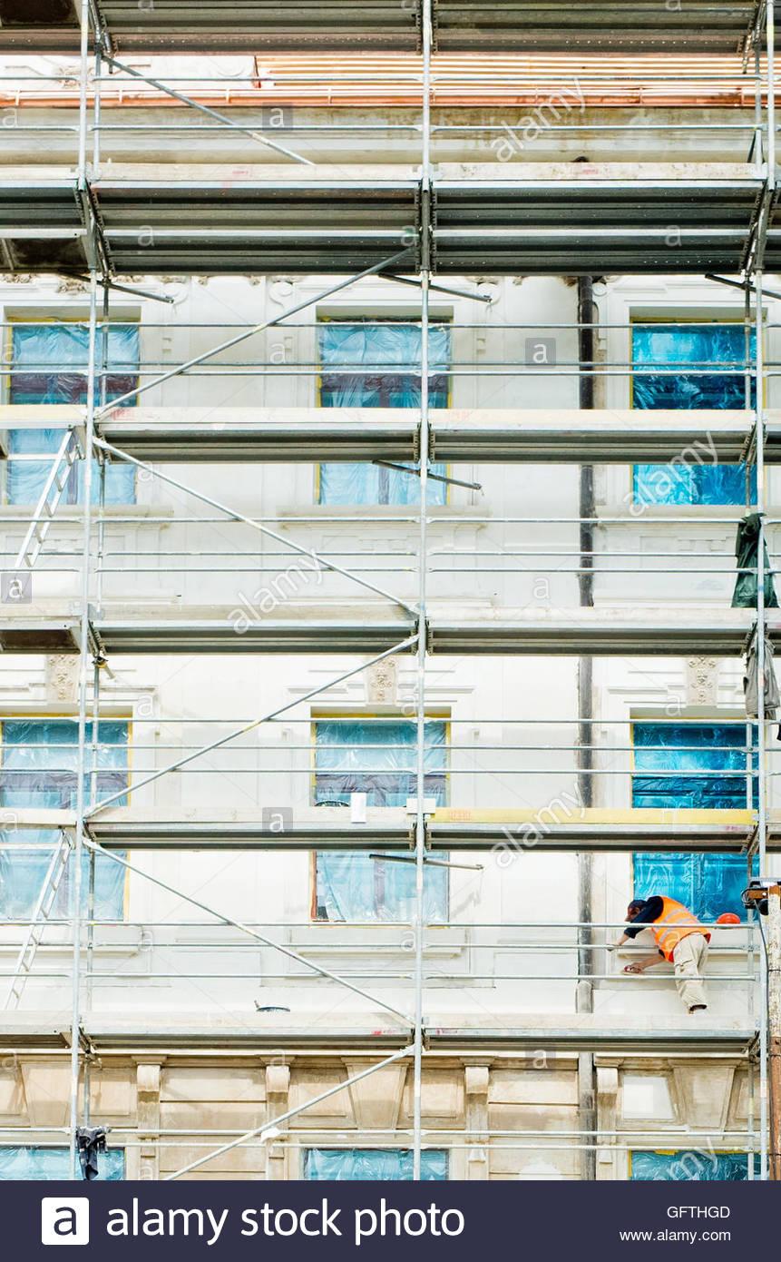 Arbeiter auf Gerüsten eines Hauses im Wiederaufbau Stockbild