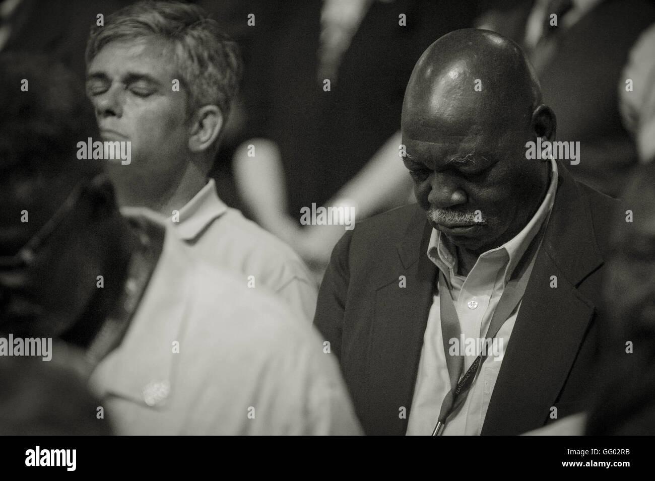 Eine afrikanische amerikanische/schwarzer Mann und kaukasischen/weiß man nebeneinander sitzen im Gebet bei Stockbild