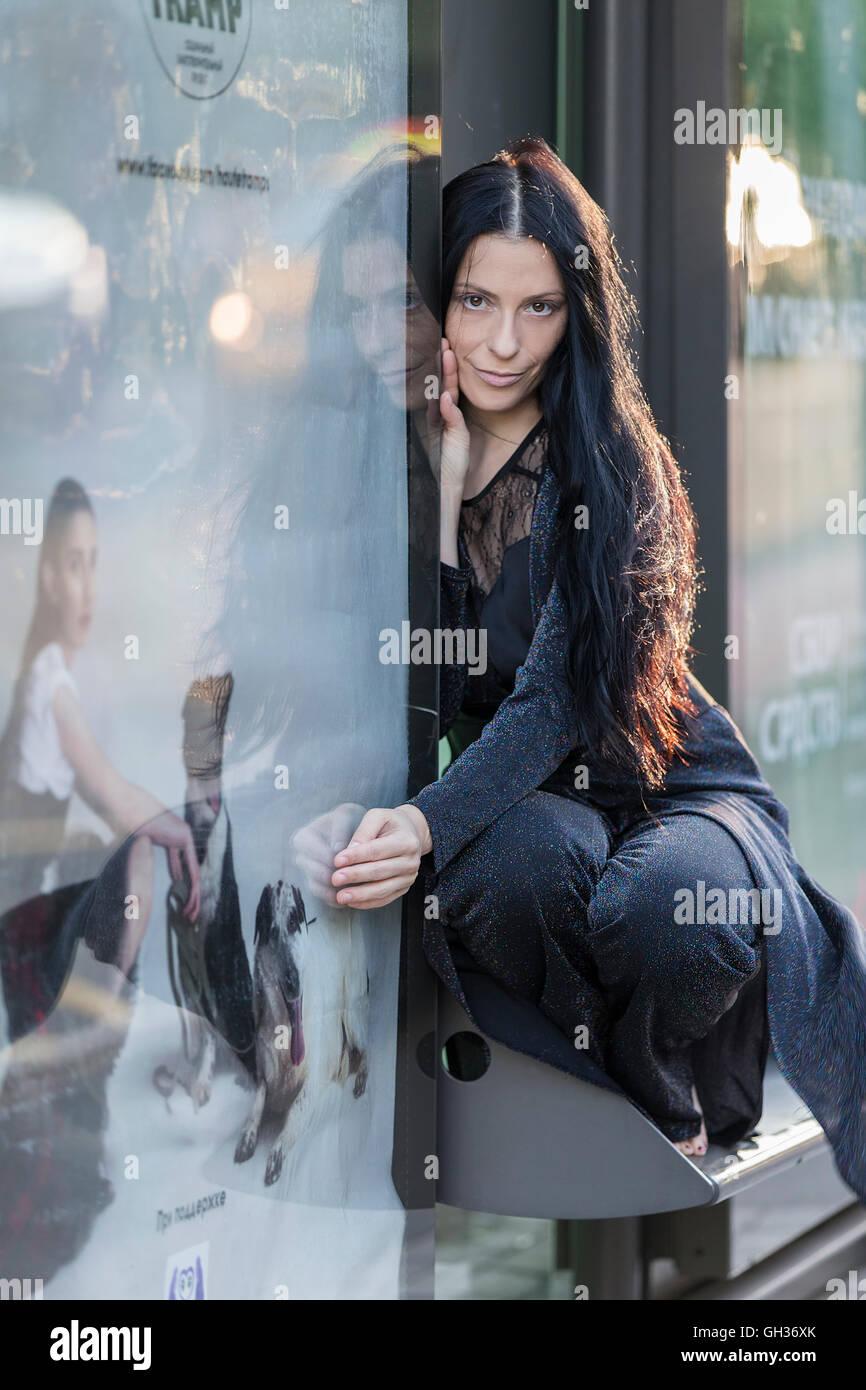 Dunkelhaarige Frau mit der Reflexion aus dem Glas. Stockbild