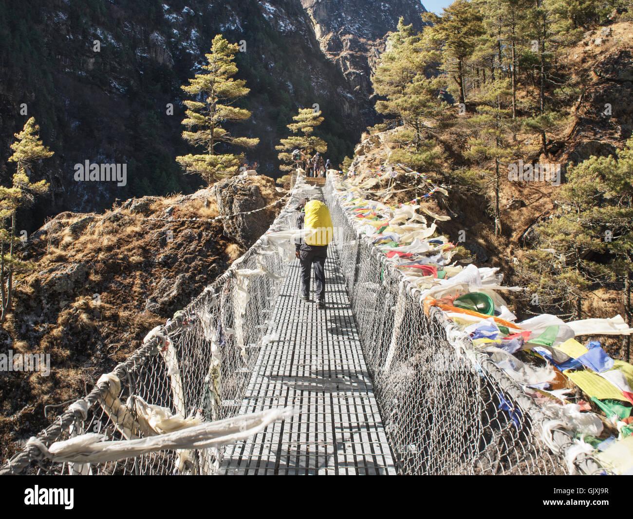 Ein Wanderer durchquert eine Hängebrücke in Nepal Everest-Basislager Stockbild