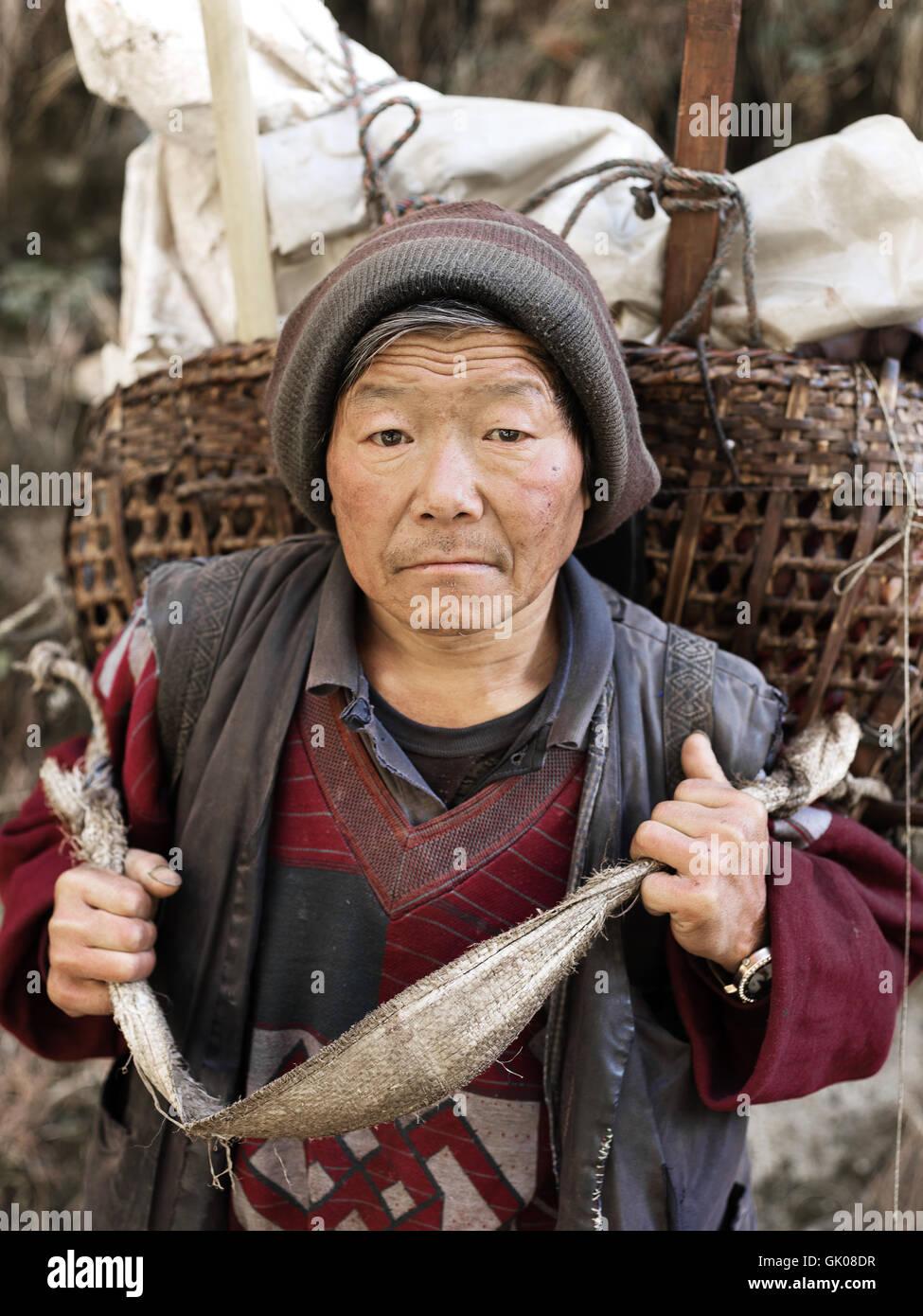 Ein Mann in der Nähe von Lukla, Nepal trägt seine Produkte über den Himalaya-Bergen in einem Korb Stockbild