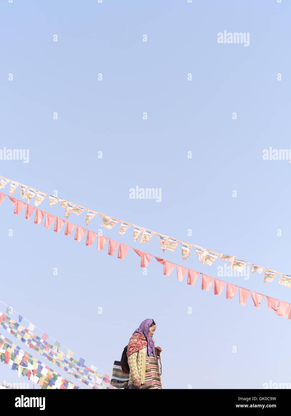 Eine Frau steht unten Gebetsfahnen draußen Boudhanath Pagode in Kathmandu, Nepal Stockbild