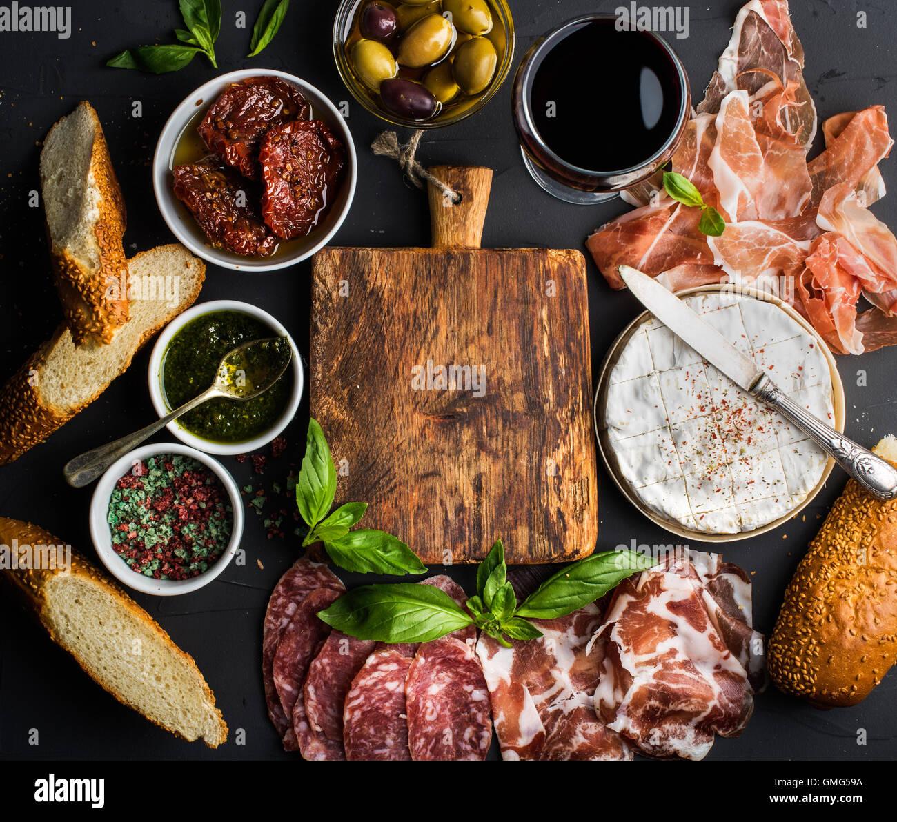 Wein snack Set mit leeren Holzbrett in Mitte. Glas Rot, Fleischauswahl, mediterranen Oliven, getrocknete Tomaten, Stockbild