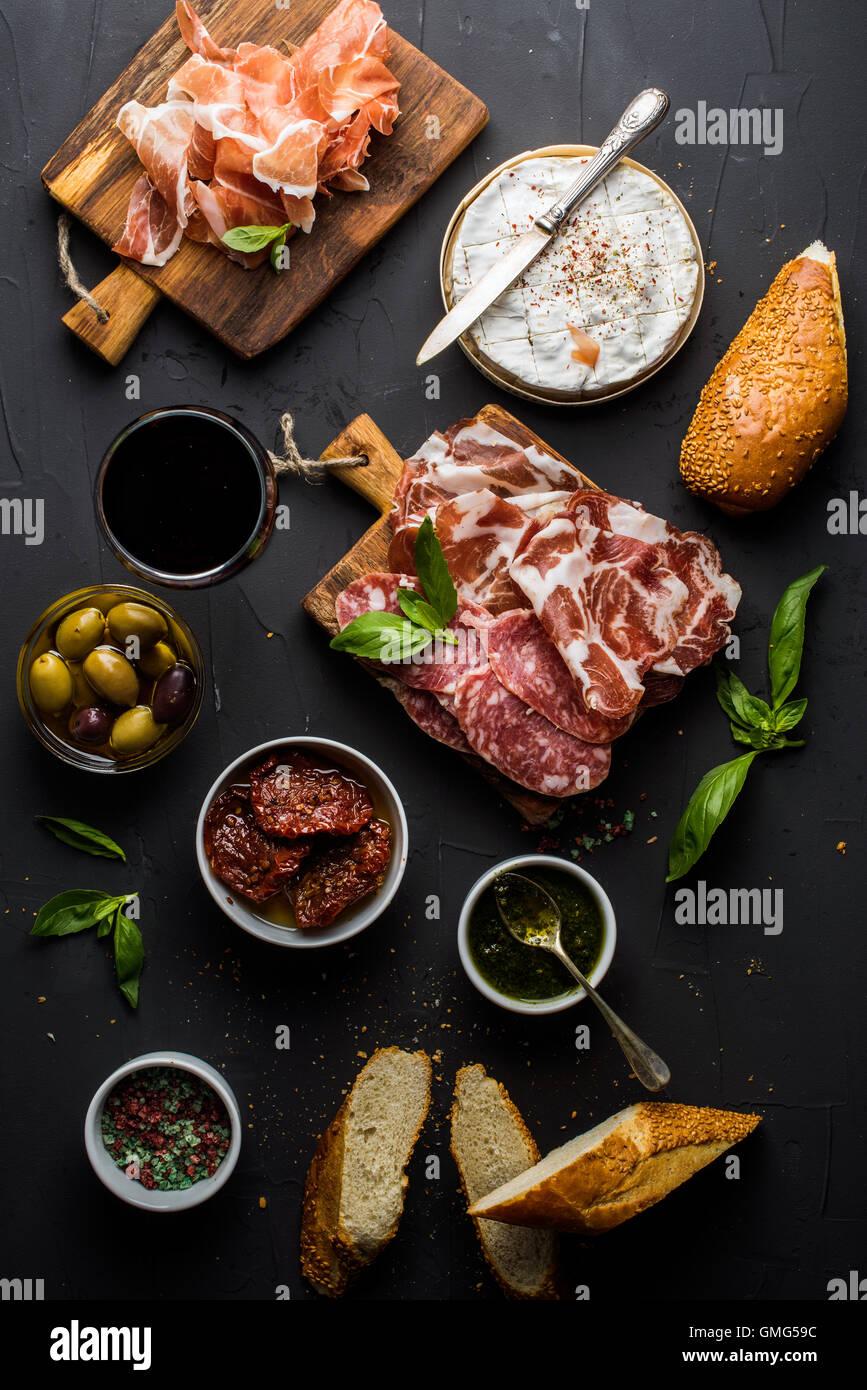 Wein snack Set. Glas Rot, Fleischauswahl, mediterranen Oliven, getrocknete Tomaten, Baguette Scheiben, Camembert Stockbild