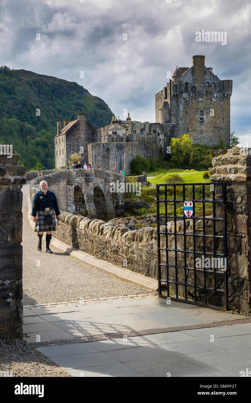 Mann in einem Kilt geht über die Brücke von Eilean Donan Castle, Highlands, Schottland, UK Stockbild