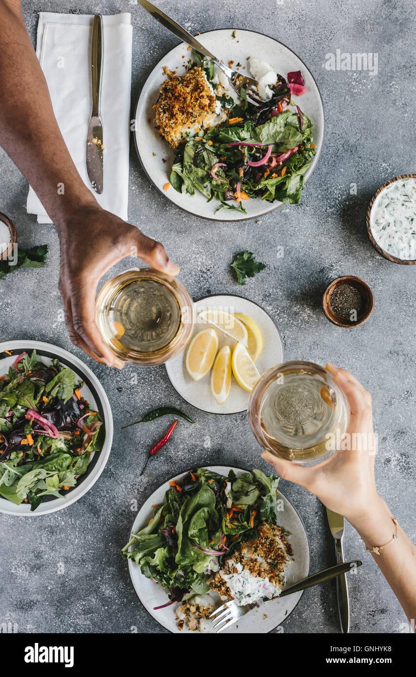 2 Personen sind gebratener Fisch, Salat, Wein zum Abendessen genießen. Stockbild