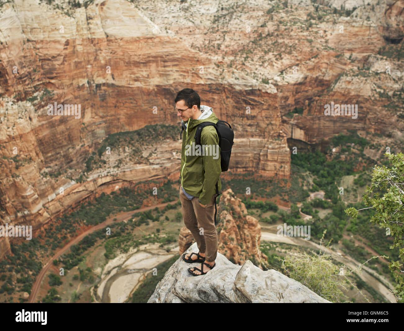 Ein Wanderer steht an der Spitze eines Peaks im Zion National Park in Utah Stockbild