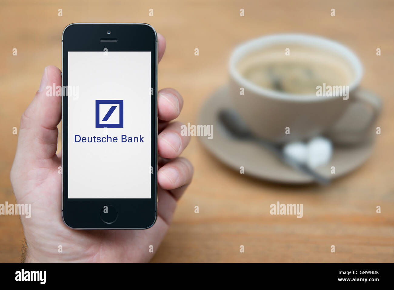 Ein Mann schaut auf seinem iPhone das Logo der Deutschen Bank zeigt, während bei einer Tasse Kaffee (nur zur Stockbild