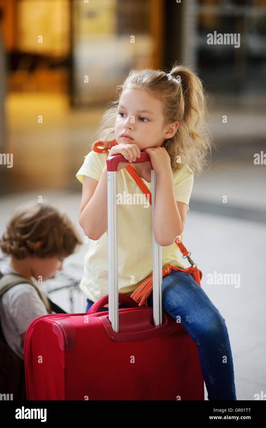 Charmante girlie 7-8 Jahre sitzt neben ihr Gepäck am Bahnhof. Mädchen überlegte oder müde. Sie Stockbild