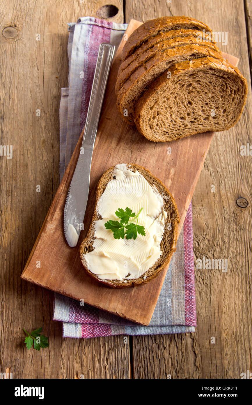 Butter und Brot zum Frühstück, mit Petersilie über rustikale Holz Hintergrund Stockbild