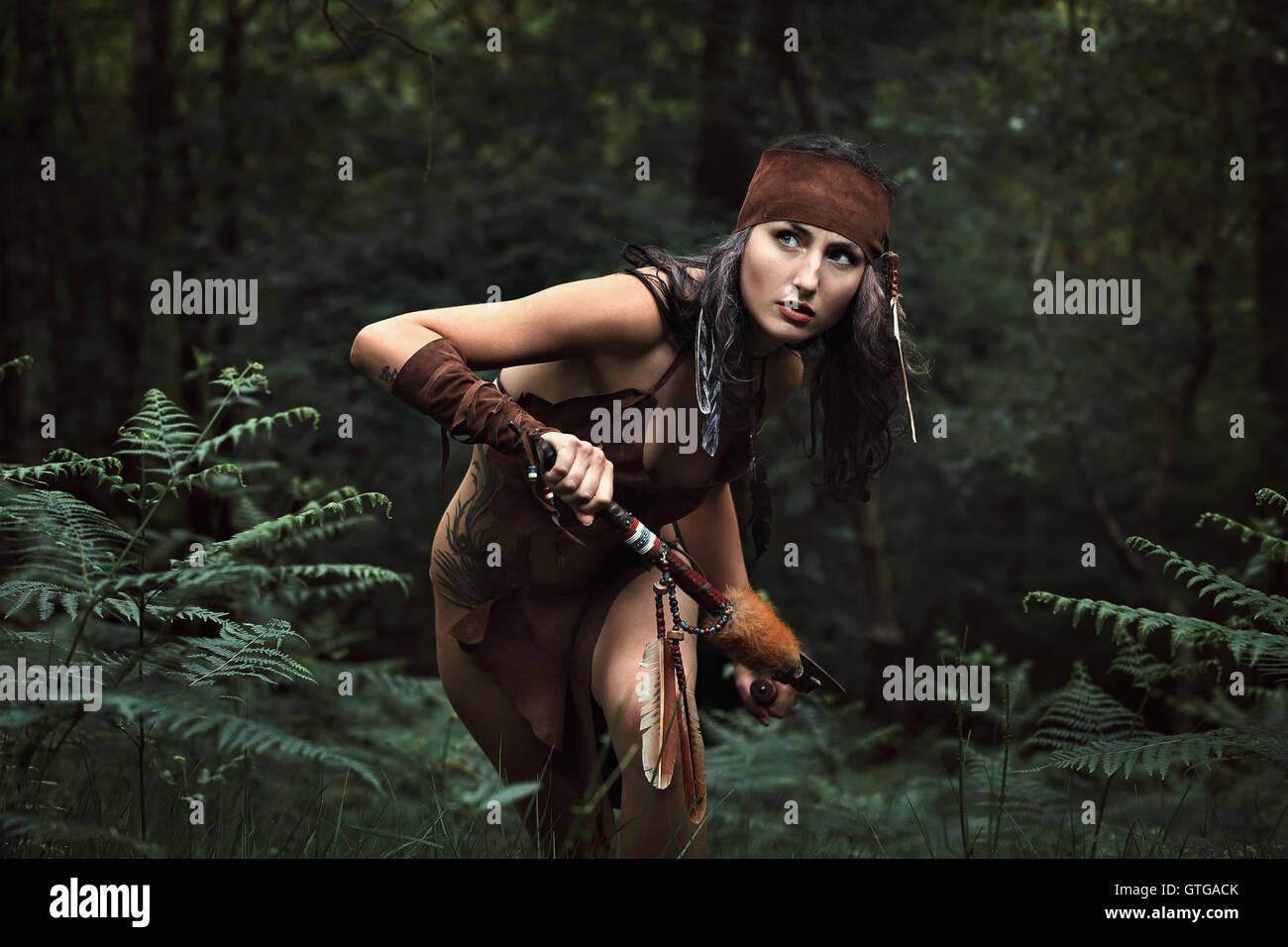 Schöne indische Jägerin in einem grünen Wald. Native Krieger Stockbild