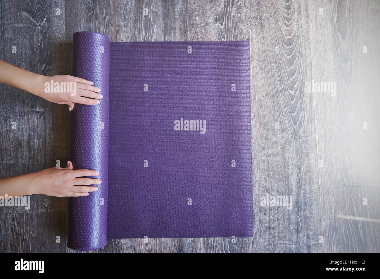 Frau Rollen ihre Matte nach einem Yoga-Kurs Stockbild