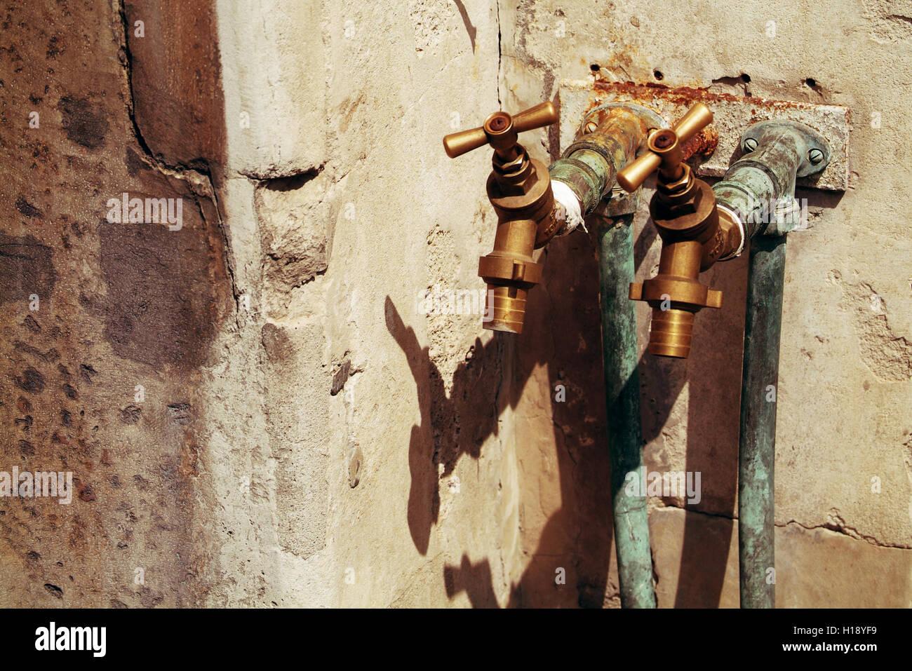 zwei traditionelle rostige Wasserhähne an der gelben Stein Wand befestigt Stockbild