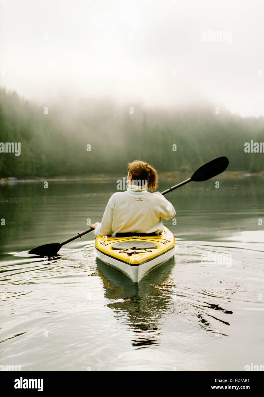 Ein Gast im Nimmo Bay Resort gilt für ein Morgen-Kajak. Nimmo Bay ist ein Angler-Paradies inmitten der Wildnis Stockbild