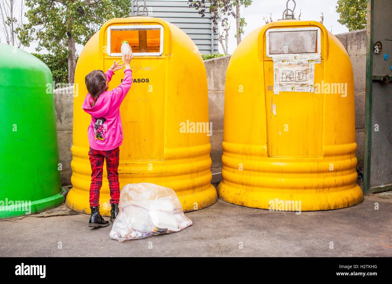 Behälter aus Kunststoff für Mülltrennung. Mädchen legt Kunststoff in einen Auffangbehälter Stockbild