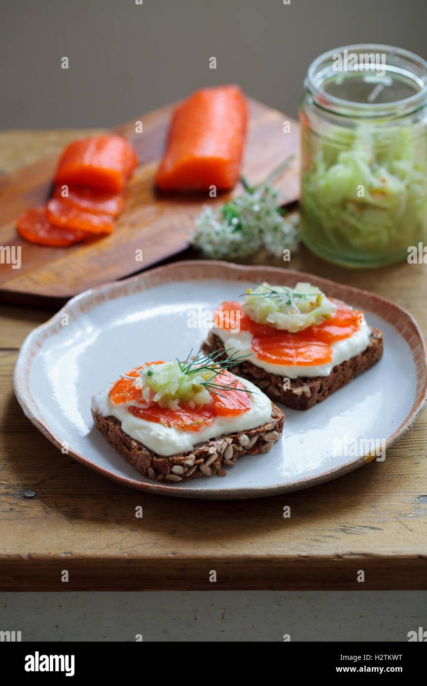 Skandinavische dunkles Brot mit ausgehärteten Forelle, Mikro Kräuter, Gurken-Chutney und Meerrettich-Creme Stockbild